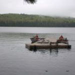 Two motorboats pushing the dock into place on Lake Opeongo