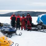The Weclome Lake field crew standing next to an ice hut and snowmobiles