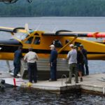 Field crew strapping a boat to the pontoons of a float plane