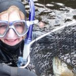Photo of a student in mask and snorkel holding a smallmouth bass in a net