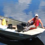 Photo of two students in a motorboat on a calm lake